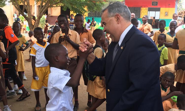 man shaking hands with children